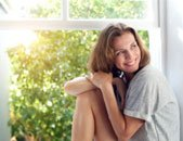 photo of happy woman sitting near window