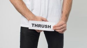 man grabbing crotch holding sign saying 'thrush' in front