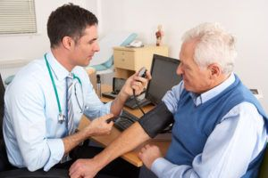 Doctor taking blood pressure senior man
