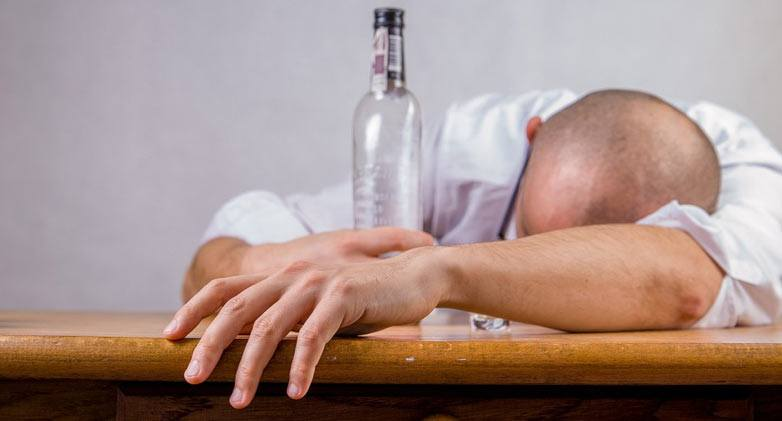 Man asleep at desk holding bottle with a hangover