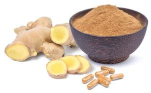 Photo of ginger root, ginger powder in bowl, and capsules of ginger powder